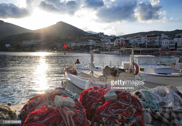fisherman and anchored boats in datca marina at sunset . - emreturanphoto stock pictures, royalty-free photos & images