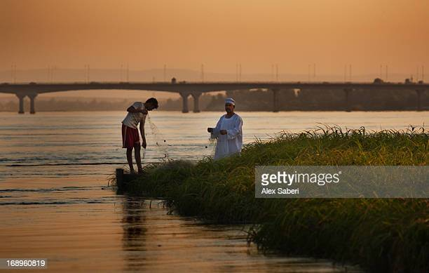 a fisherman and his son check their fishing nets along the nile river. - alex saberi photos et images de collection
