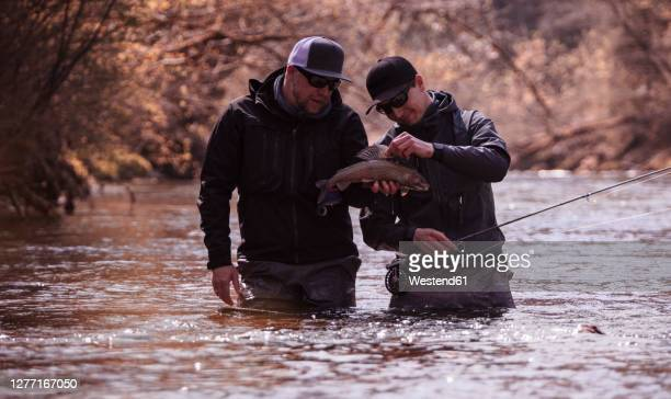 fisherman and son holding caught fish while standing in river at forest - releasing stock pictures, royalty-free photos & images