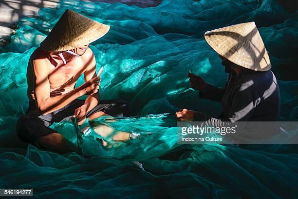 Fisherman and woman in mending his fishing net