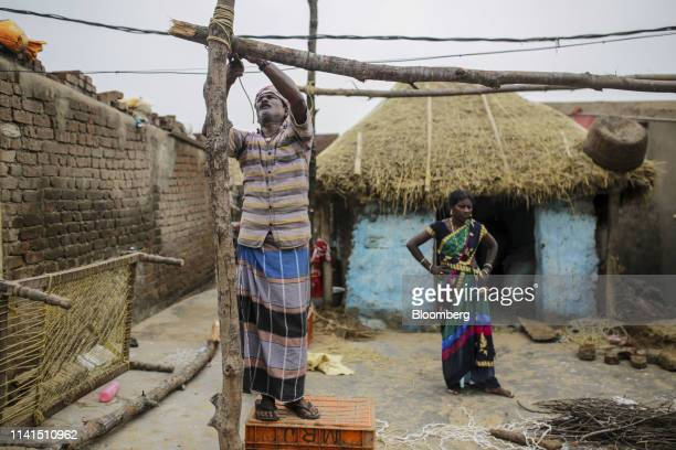 A fisherman arranges wood at a damaged house in Konark Odisha India on Sunday May 5 2019 Authorities launched a massive restorationandrelief effort...
