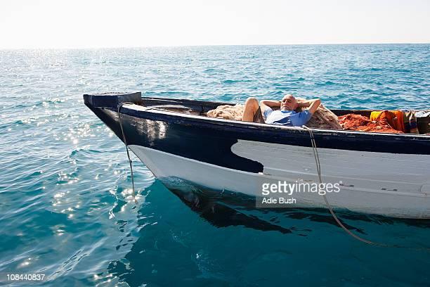 fisherman asleep on nets - een dutje doen stockfoto's en -beelden