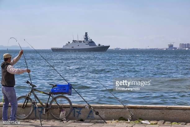 fisherman at bay of izmir with frigate at the background. - emreturanphoto stock pictures, royalty-free photos & images