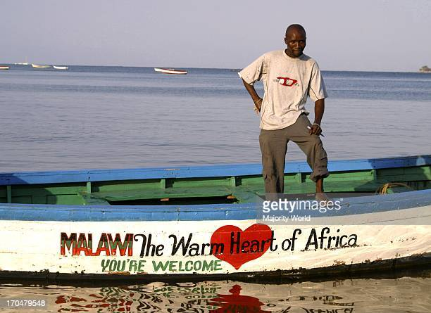 A fisherman at Cape Maclear stands on his boat with the national slogan written on his boat Malawi the warm heart of Africa Cape Maclear is a small...