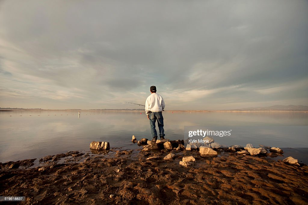 Fisherman at dry lake during drought : Stock Photo