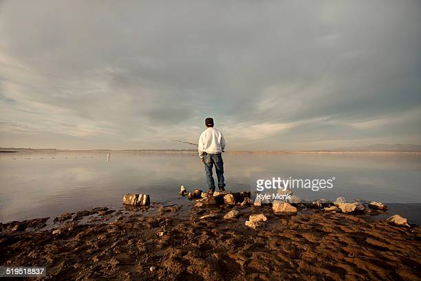 Fisherman at dry lake during drought