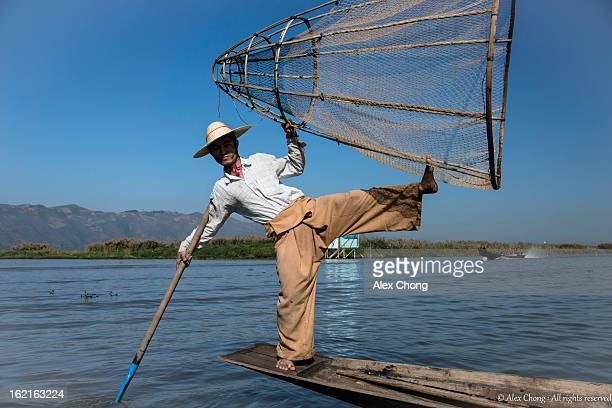 Fisherman at Inle Lake, Myanmar, poses in a dramatic acrobatic manner to show off his skills balancing the tools of his trade.