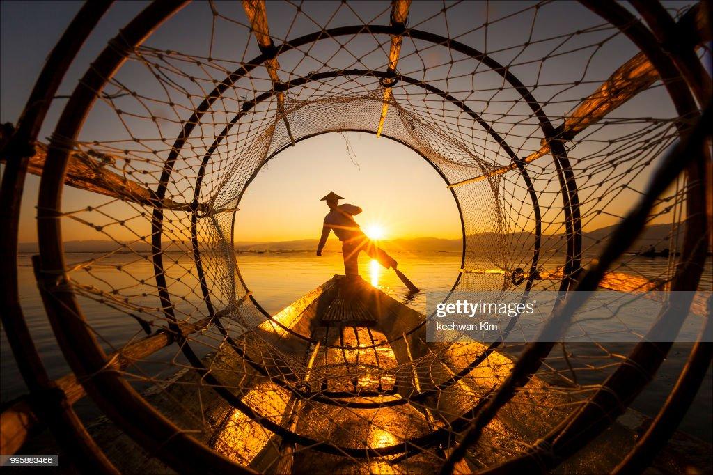 A fisherman at sunset on Inle Lake, Myanmar. : Stock Photo