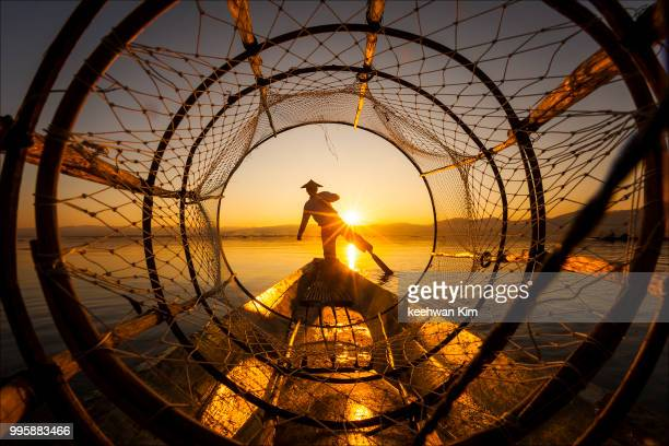 a fisherman at sunset on inle lake, myanmar. - grande angular - fotografias e filmes do acervo