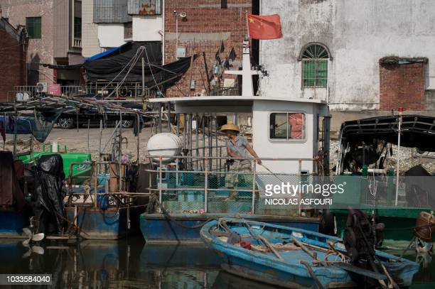 A fisherman attach all the boats together ahead of the arrival of the Super Typhoon Mangkhut in Sanhe village on the outskirts of Zhanjiang in...