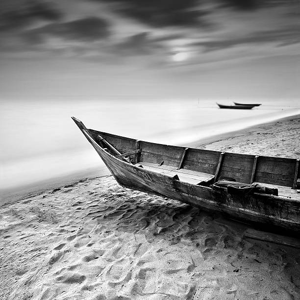 Fisherman boat at beach in black and white