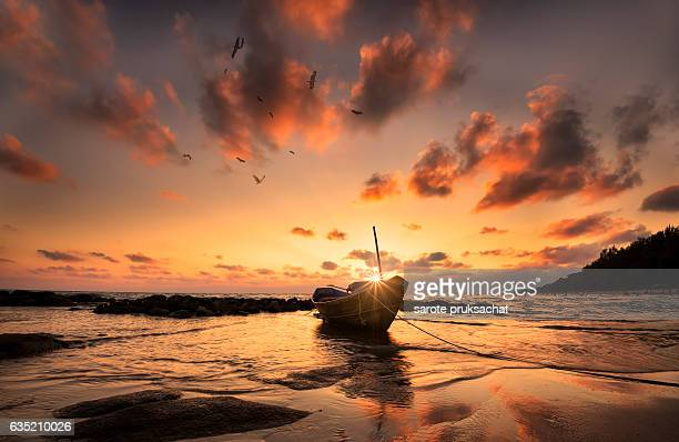Fisherman boat at beach sunset Thailand .