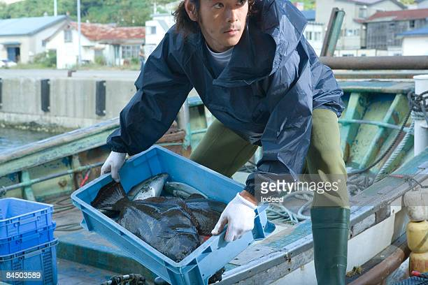 Fisherman carrying crate of fish from boat