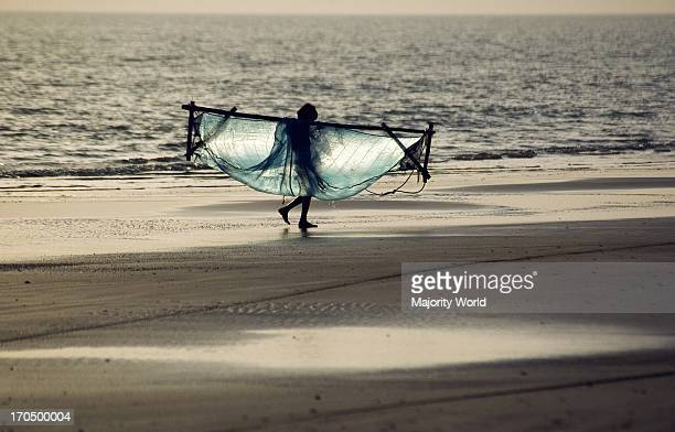 A fisherman carrying his net at Kuakata beach in Patuakhali Bangladesh Kuakata locally known as Sagar Kannya or daughter of the sea is one of the...