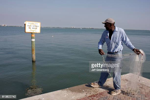 A fisherman casting a net at Fort Pierce City Marina