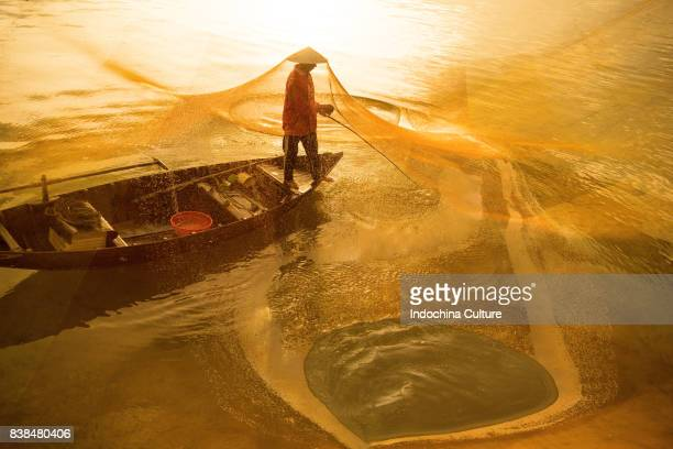 Fisherman casting fishing net in dawn at Cua Dai, Hoi An, Vietnam