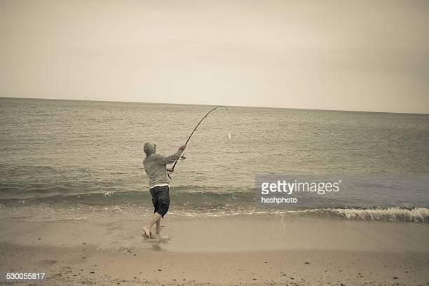 Fisherman casting fishing rod on beach, Truro, Massachusetts, Cape Cod, USA