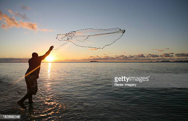 Fisherman casting his net at sunset