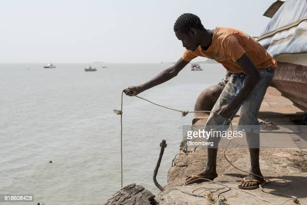 A fisherman casts a line by the harbour in the port area of Bissau GuineaBissau on Saturday Feb 10 2018 The International Monetary Fund said an...