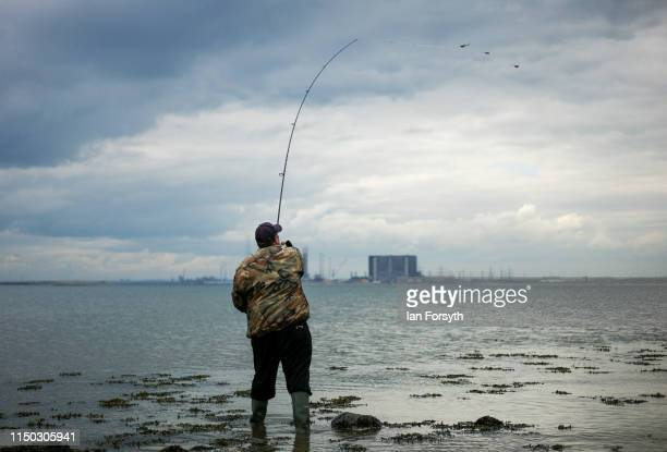 A fisherman casts out from Bran Sands beach at South Gare on May 19 2019 in Redcar England South Gare is a man made point of land reaching into the...