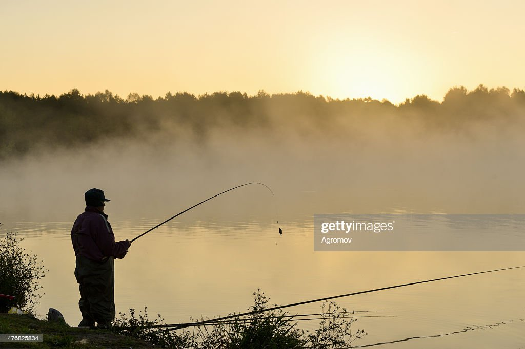 Fisherman catches fish on the lake at sunset : Stock Photo