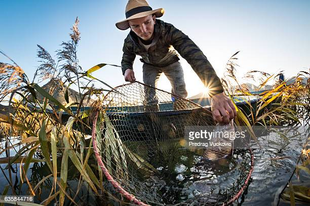 Fisherman catching carp fish