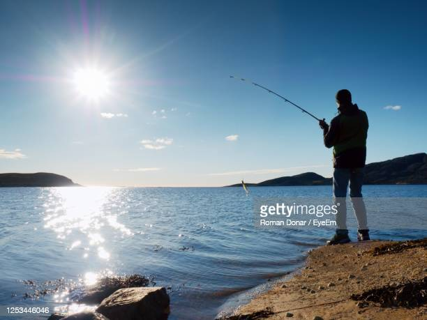 fisherman check pushing bait on  fishing line, prepare rod and than throw lure into peacefull water. - 淡水釣り ストックフォトと画像