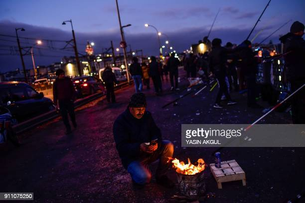 TOPSHOT A fisherman checks his mobile phone as he warms up by a brazier on Galata Bridge in the Eminonu District of Istanbul on January 27 2018 / AFP...