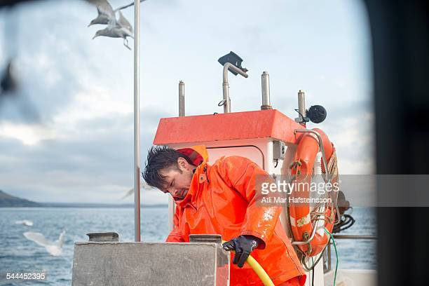 Fisherman cleaning fishing boat