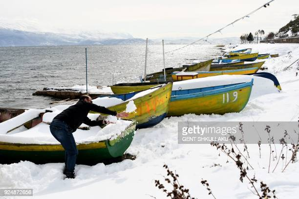 A fisherman cleans the snow from his boat on the shore of Ohrid Lake in Pogradec southeast Albania on February 27 2018 Dubbed The Beast from the East...