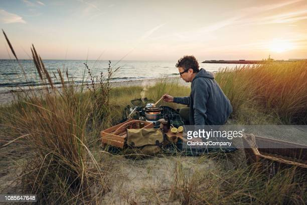fisherman cooking his catch at the beach - zealand denmark stock pictures, royalty-free photos & images