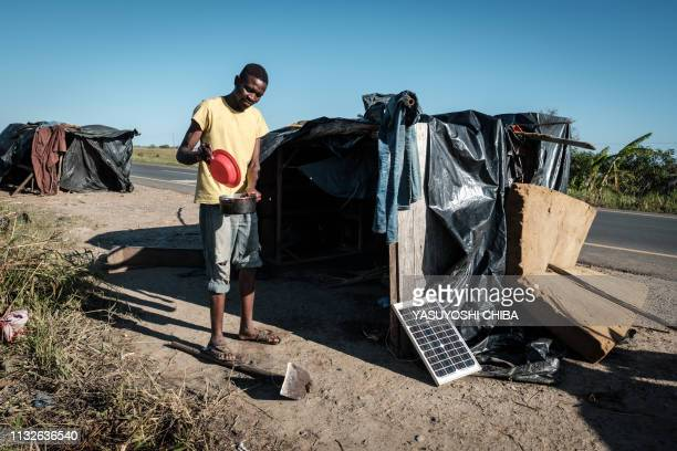 A fisherman cooks fish to bring to his family who stay at an evacuation site as he lives in a makeshift home beside the road after losing his home...
