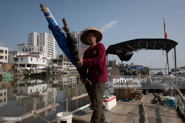 A fisherman dismantle the roof of his boat ahead of the arrival of the Super Typhoon Mangkhut in Sanhe village on the outskirts of Zhanjiang in...