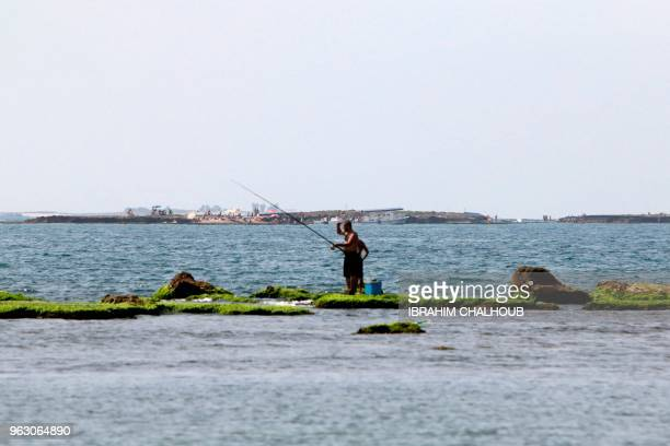 A fisherman fishes on Bellan island off the El Mina district coast on May 27 2018