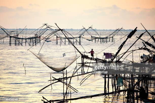Fisherman fishing fish by big net at sunrise, Pak Pra, Phatthalung, Thailand