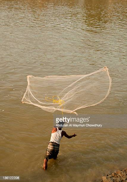fisherman fishing in  monu river - fishing in bangladesh stock photos and pictures