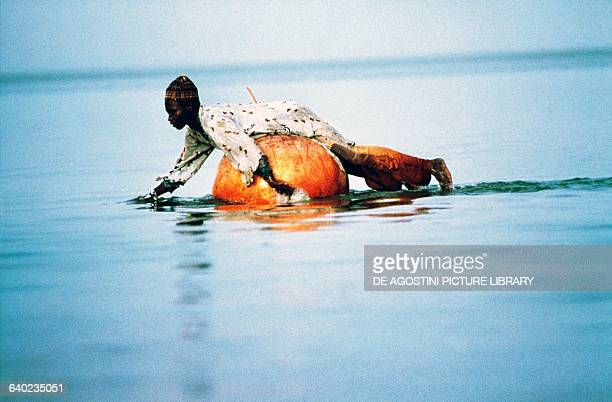 Fisherman from Kogeron island floating on a pumpkin used to hold the fish caught in the nets Lake Chad Chad