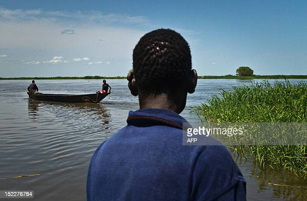 Fisherman from the Mundari tribe watches a small boat carrying fruits in Terekeka, a fishing community 75km north of Juba in South Sudan, on...