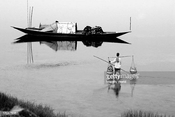A fisherman going to the boat after selling his fish in a local market in Shohagpur Sirajgonj Bangladesh 2009