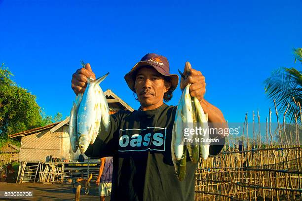 fisherman holding a fresh caught fish