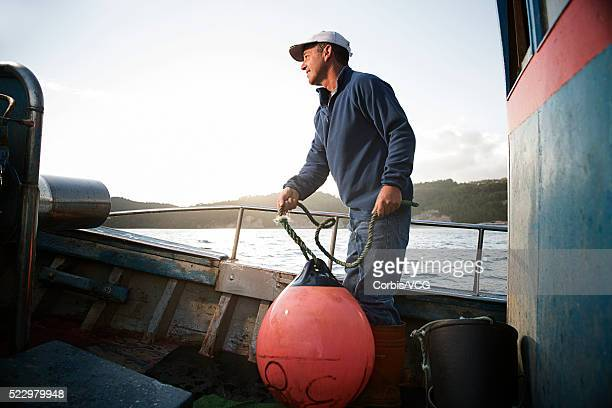 fisherman holding buoy in hand - one man only stock pictures, royalty-free photos & images