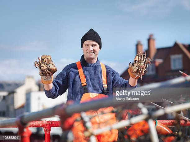 Fisherman holding crabs on boat