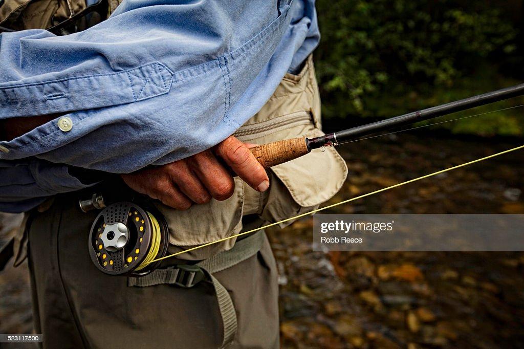 Fisherman holding rod : Stock Photo