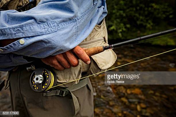 fisherman holding rod - robb reece stock photos and pictures