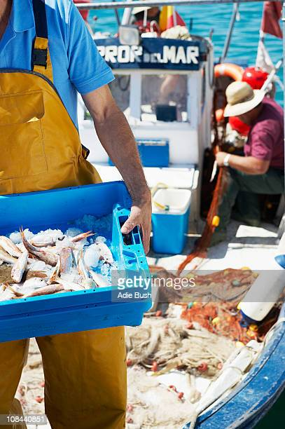 Fisherman holding tray of fresh fish