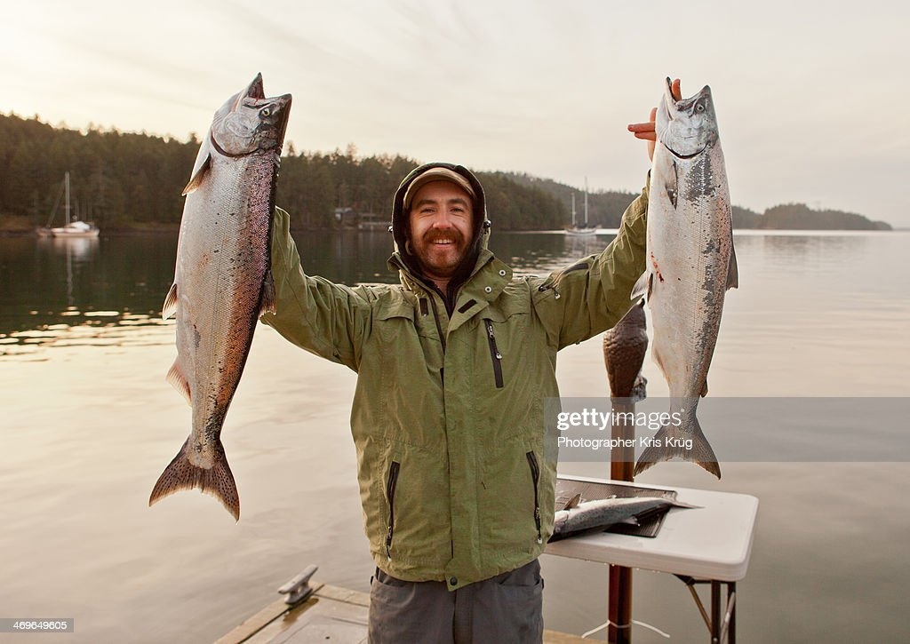 Fisherman holding up king salmon chinook fish stock photo for Fishing kings free