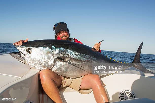 Fisherman holds a large fresh fish caught from a boat on the Atlantic ocean