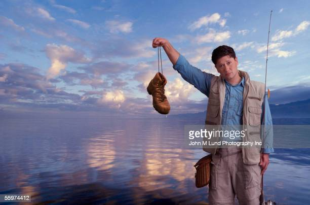 fisherman holds an old boot - bad luck stock pictures, royalty-free photos & images