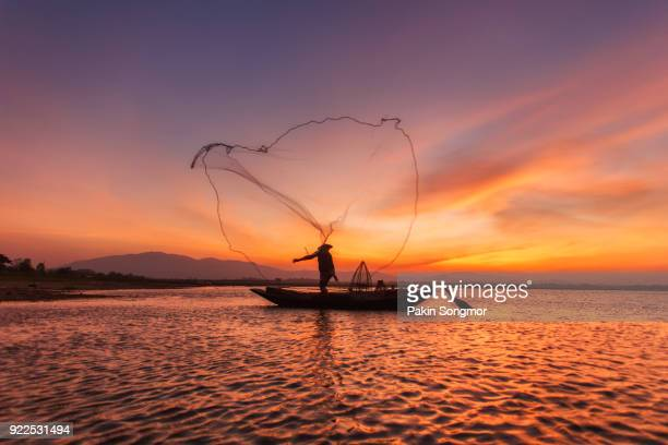 a fisherman in a boat on the lake at sunset - myanmar culture stock photos and pictures