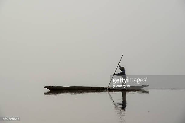 Fisherman in a pirogue on the foggy Congo River